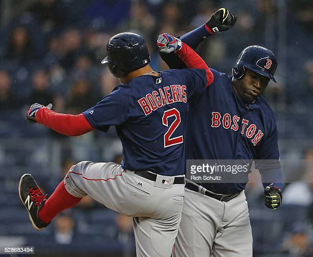 David Ortiz of the Boston Red Sox celebrates with teammate Xander Bogaerts after both scored on Ortiz's two run home run in the first inning against...