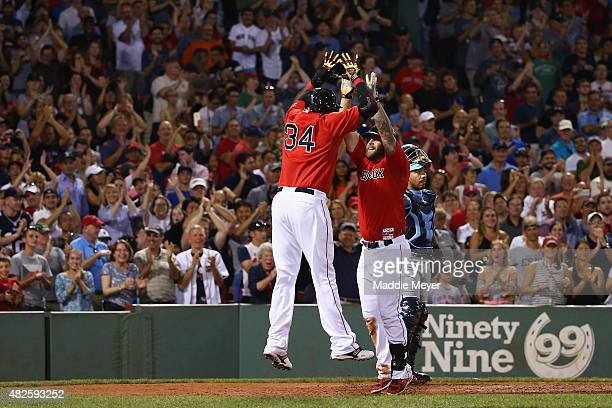 David Ortiz of the Boston Red Sox congratulates Mike Napoli after he hit a two run homer during the seventh inning against the Tampa Bay Rays at...