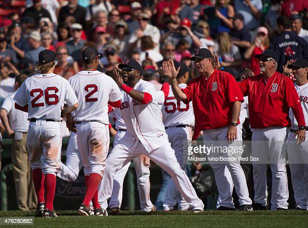 David Ortiz of the Boston Red Sox congratulates Xander Bogaerts after his tworun double as part of a seven run eighth inning helped the team to a 74...
