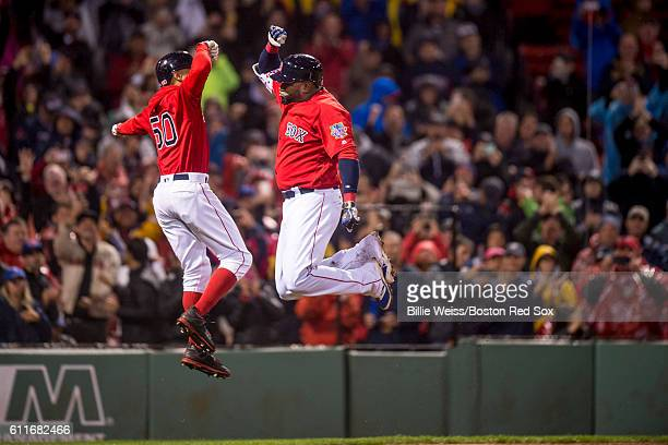 David Ortiz of the Boston Red Sox high fives Mookie Betts after hitting a go ahead two run home run during the seventh inning of a game against the...
