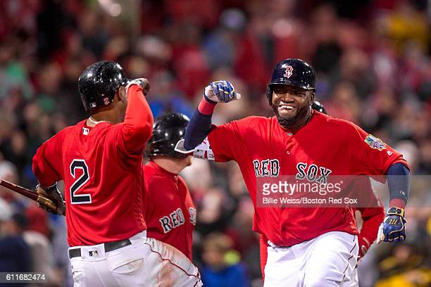 David Ortiz of the Boston Red Sox high fives Xander Bogaerts after hitting a go ahead two run home run during the seventh inning of a game against...