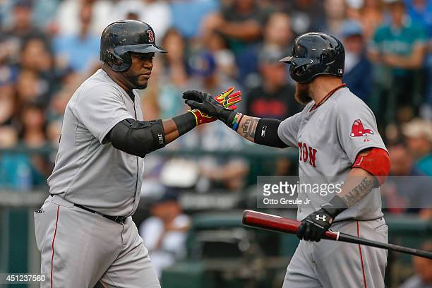David Ortiz of the Boston Red Sox is congratulated by Jonny Gomes after hitting a tworun homer in the first inning against the Seattle Mariners at...