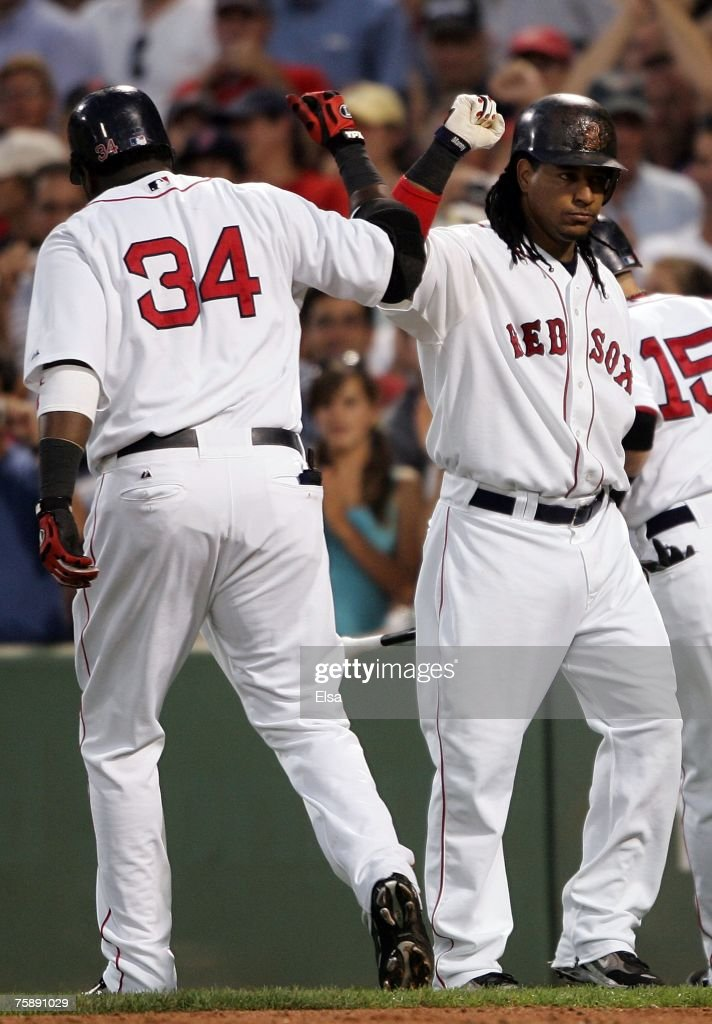 David Ortiz #34 of the Boston Red Sox is congratulated by teammate Manny Ramirez #24 after Ortiz hit a two run homer in the third inning against the Baltimore Orioles on July 31, 2007 at Fenway Park in Boston, Massachusetts.