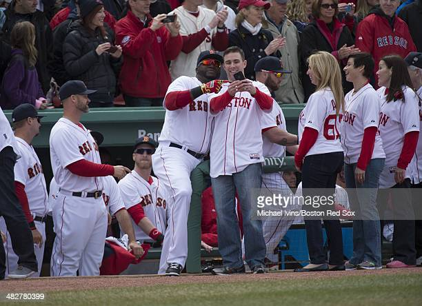David Ortiz of the Boston Red Sox poses for a photo with a Boston Marathon bombing responder during a ceremony honoring the 2013 World Series...