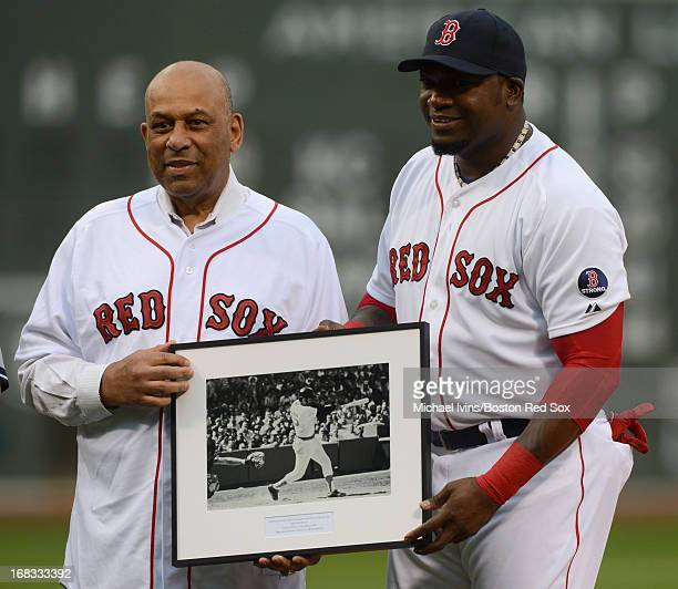 David Ortiz of the Boston Red Sox presents Orlando Cepeda with a photograph during a ceremony honoring Cepeda as the first Designated Hitter in the...