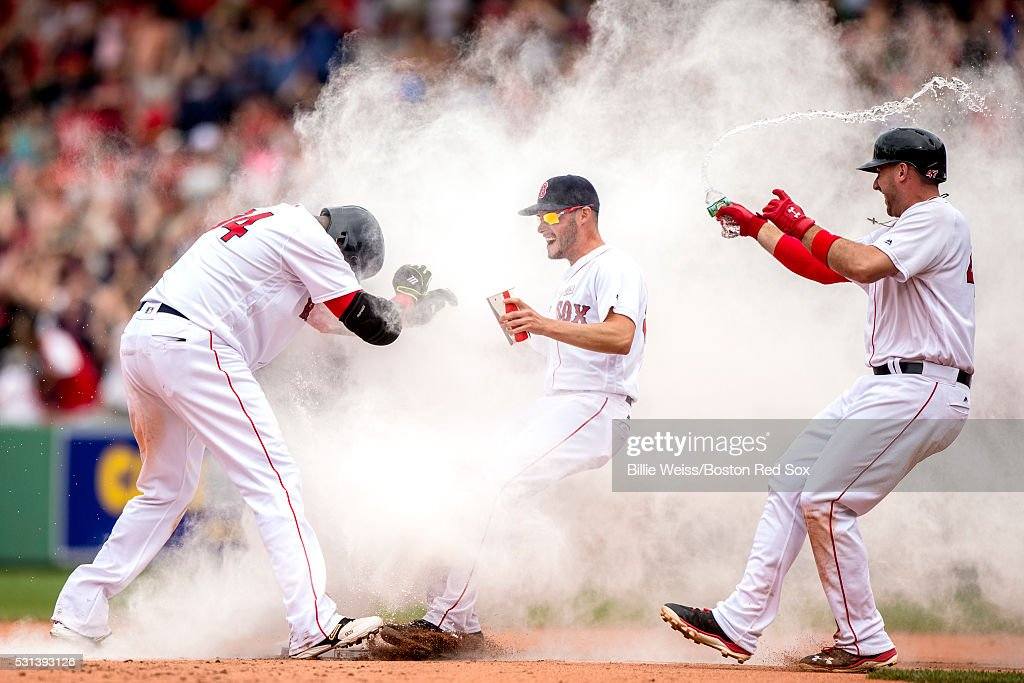 David Ortiz #34 of the Boston Red Sox reacts as he is mobbed by Joe Kelly #18 and Travis Shaw #47 after hitting a game winning walk-off single during the eleventh inning of a game against the Houston Astros on May 14, 2016 at Fenway Park in Boston, Massachusetts.