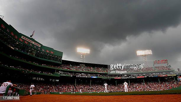 David Ortiz of the Boston Red Sox receives an intentional walk as the clouds and rain roll over the field during a game against the Colorado Rockies...