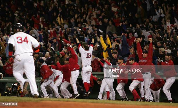 David Ortiz of the Boston Red Sox runs to first base as the dugout celebrates his game winning tworun home run in the twelth inning to defeat the New...