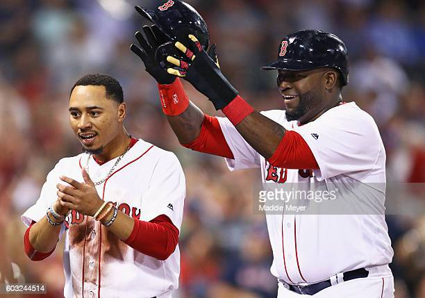 David Ortiz of the Boston Red Sox takes off Mookie Betts' #50 helmet after they both scored against the Baltimore Orioles during the first inning at...