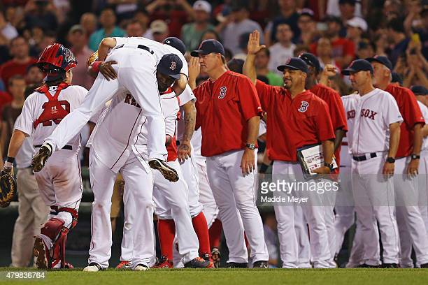 David Ortiz of the Boston Red Sox throws Koji Uehara over his shoulder at the end of their game against the Miami Marlins at Fenway Park on July 7...