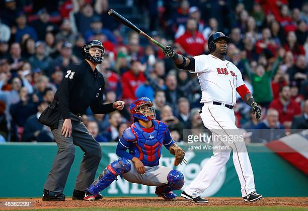 David Ortiz of the Boston Red Sox watches the ball after hitting a threerun home run in the 8th inning against the Texas Rangers at Fenway Park on...