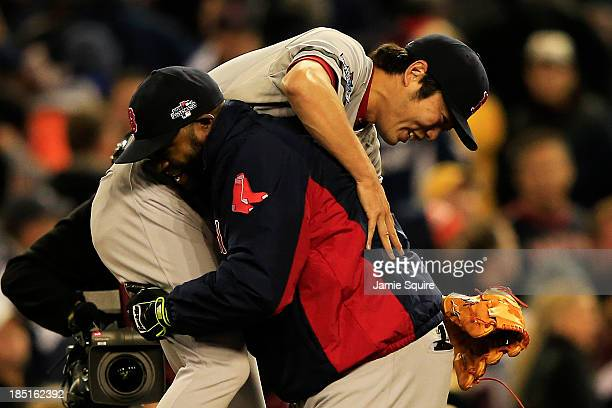 David Ortiz picks up Koji Uehara of the Boston Red Sox as they celebrate their 4 to 3 win over the Detroit Tigers during Game Five of the American...