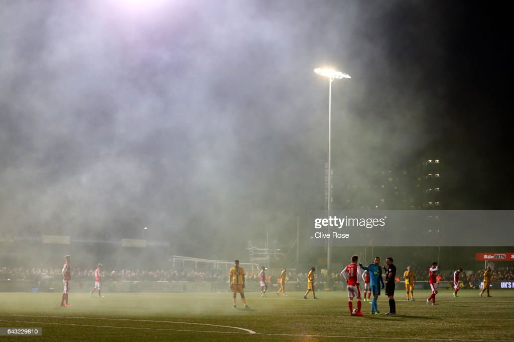 David Ospina of Arsenal speaks with referee Michael Oliver as smoke from a smoke bomb fills the air during the Emirates FA Cup fifth round match between Sutton United and Arsenal on February 20, 2017 in Sutton, Greater London.