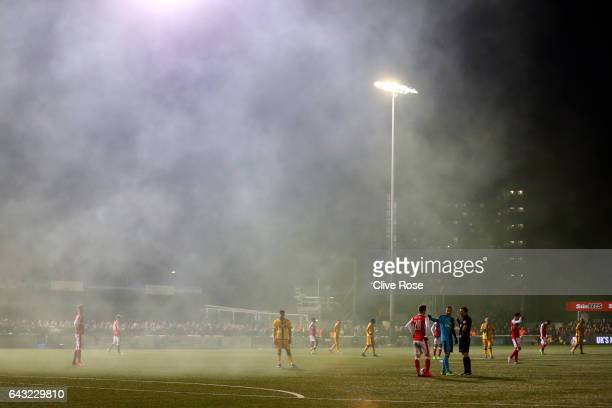 David Ospina of Arsenal speaks with referee Michael Oliver as smoke from a smoke bomb fills the air during the Emirates FA Cup fifth round match...