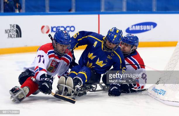 David Palat and Zdenek Habl of Czech Republic battles for the puck with Peter Nilsson of Sweden in the Ice Hockey Classification game between Czech...