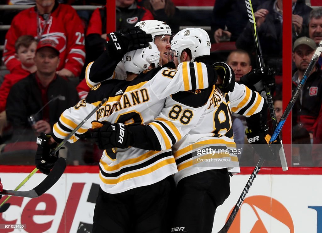 David Pasternak #88 of the Boston Bruins is congratulated by teammates Brad Marchand #63 and Riley Nash #20 after scoring a goal during an NHL game against the Carolina Hurricanes on March 13, 2018 at PNC Arena in Raleigh, North Carolina.