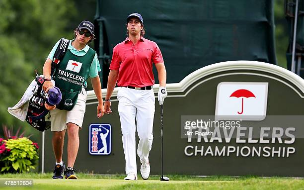 David Pastore walks from the 18th tee with his caddie during the first round of the Travelers Championship at TPC River Highlands on June 25 2015 in...