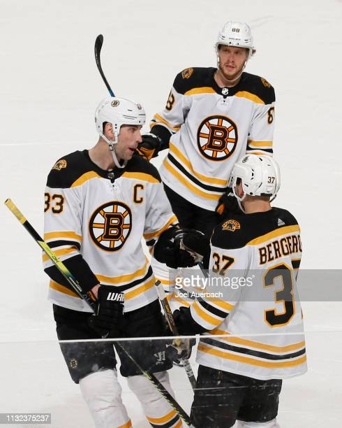David Pastrnak and Zdeno Chara congratulate Patrice Bergeron of the Boston Bruins after he scored an open net goal against the Florida Panthers at...