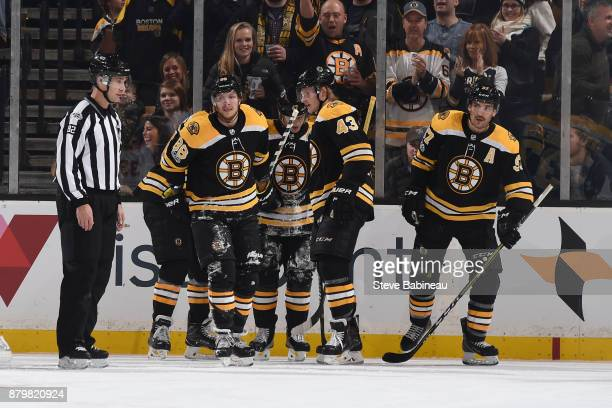David Pastrnak Danton Heinen and Patrice Bergeron of the Boston Bruins skate back to that bench after scoring a goal in the first period against the...