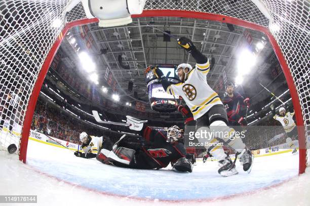 David Pastrnak of the Boston Bruins celebrates a disallowed goal due to goalie interference by Jake DeBrusk to Curtis McElhinney of the Carolina...