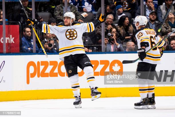 David Pastrnak of the Boston Bruins celebrates his goal against the Toronto Maple Leafs with teammate Brad Marchand during the third period at the...
