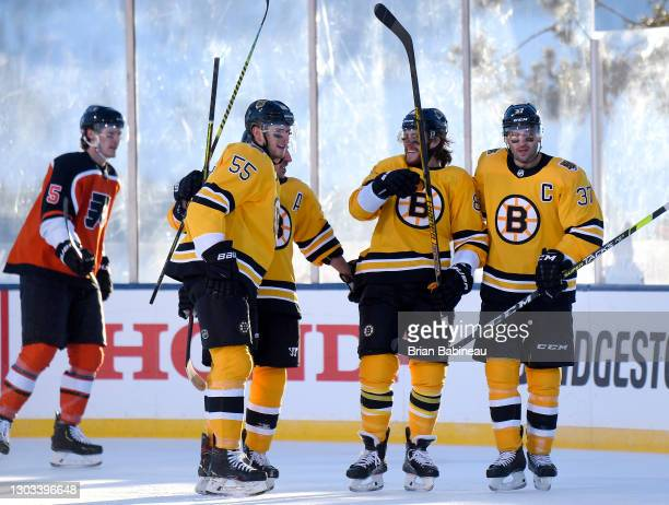 David Pastrnak of the Boston Bruins celebrates his goal against the Philadelphia Flyers with teammates Jeremy Lauzon, Brad Marchand and Patrice...