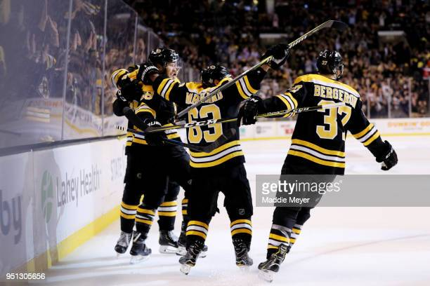 David Pastrnak of the Boston Bruins celebrates with Brad Marchand and Patrice Bergeron after scoring a goal against the Toronto Maple Leafs during...