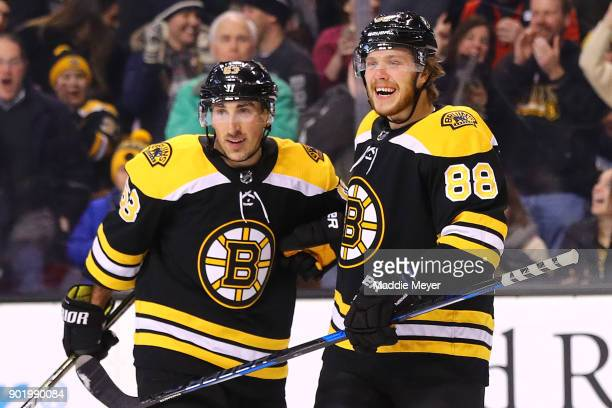 David Pastrnak of the Boston Bruins celebrates with Brad Marchand after scoring against the Carolina Hurricanesduring the first period at TD Garden...