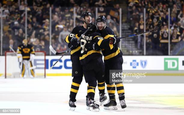 David Pastrnak of the Boston Bruins celebrates with Brandon Carlo and Zdeno Chara after scoring against the Vancouver Canucks during the third period...