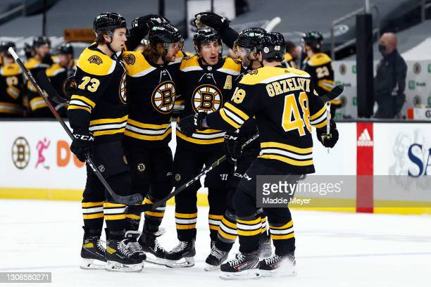 David Pastrnak of the Boston Bruins celebrates with Charlie McAvoy, Brad Marchand, and Matt Grzelcyk after scoring a goal against the New York...