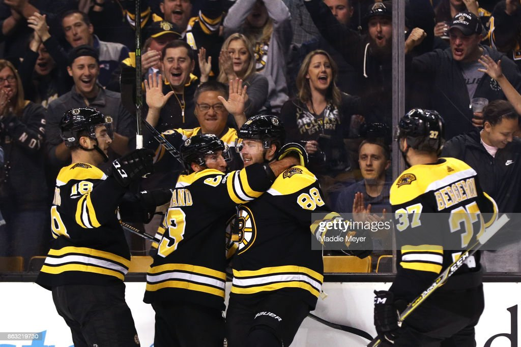 David Pastrnak #88 of the Boston Bruins celebrates with Kenny Agostino #18, Brad Marchand #63 and Patrice Bergeron #37 after scoring a goal against the Vancouver Canucks during the first period at TD Garden on October 19, 2017 in Boston, Massachusetts.