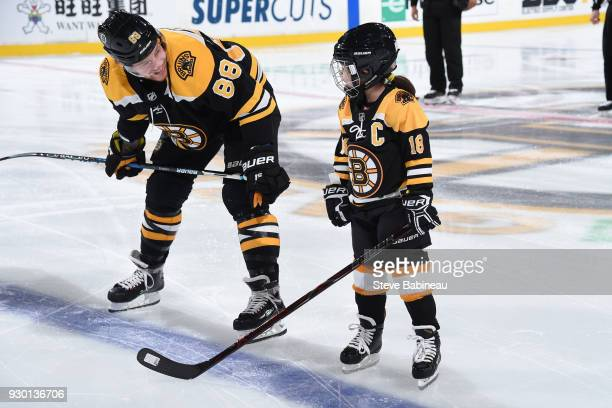David Pastrnak of the Boston Bruins chats with the kids captain before the game against the Chicago Blackhawks at the TD Garden on March 10 2018 in...