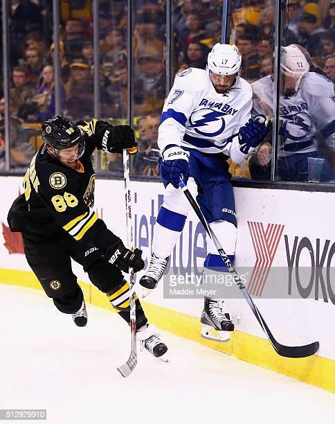 David Pastrnak of the Boston Bruins checks Alex Killorn of the Tampa Bay Lightning into the boards during the third period at TD Garden on February...