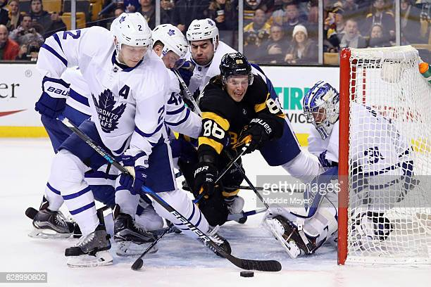 David Pastrnak of the Boston Bruins dives to take a shot against Frederik Andersen of the Toronto Maple Leafs with pressure from Matt Hunwick during...