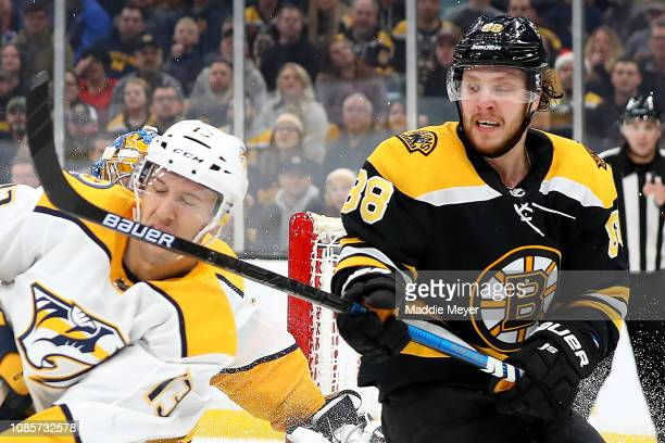David Pastrnak of the Boston Bruins hits Nick Bonino of the Nashville Predators with his stick during the first period at TD Garden on December 22...