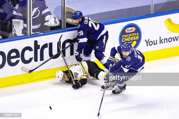 David Pastrnak of the Boston Bruins is checked by Blake Coleman of the Tampa Bay Lightning during the third period in Game Five of the Eastern...