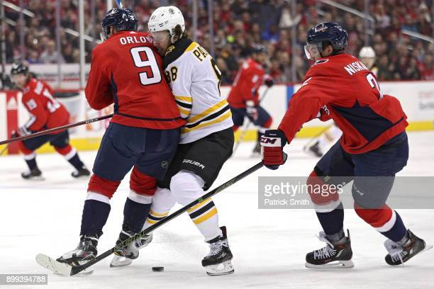 David Pastrnak of the Boston Bruins is checked by Dmitry Orlov of the Washington Capitals during the first period at Capital One Arena on December 28...