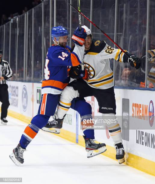David Pastrnak of the Boston Bruins is checked into the boards by Travis Zajac of the New York Islanders during the first period in Game Four of the...
