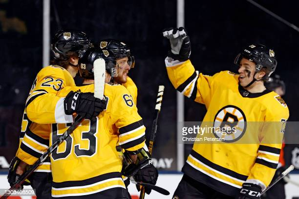 David Pastrnak of the Boston Bruins is congratulated by Jack Studnicka, Brad Marchand and Charlie McAvoy after scoring his goal third goal of the...