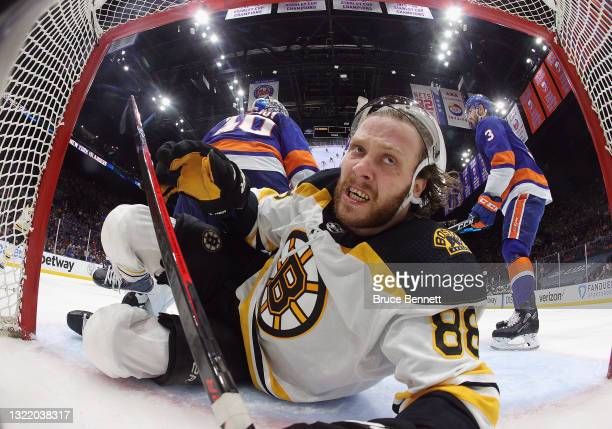 David Pastrnak of the Boston Bruins is knocked into the net during the second period against the New York Islanders in Game Four of the Second Round...