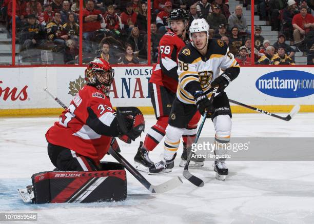 David Pastrnak of the Boston Bruins looks for a rebound against Mike McKenna and Maxime Lajoie of the Ottawa Senators at Canadian Tire Centre on...