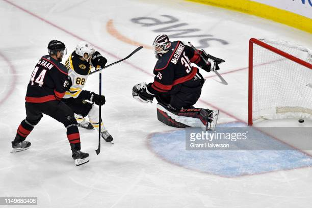 David Pastrnak of the Boston Bruins scores a goal on Curtis McElhinney of the Carolina Hurricanes during the second period in Game Four of the...