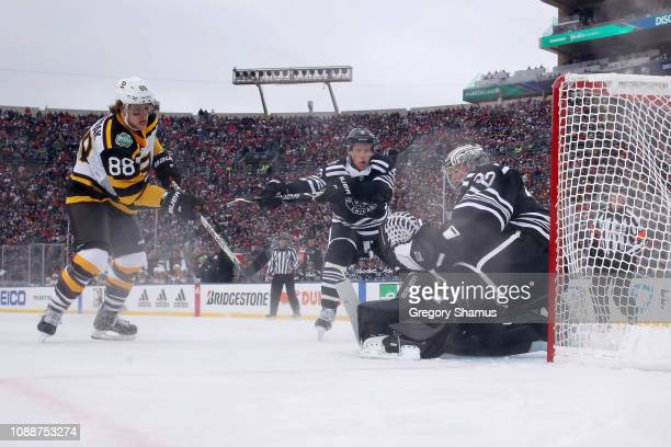 David Pastrnak of the Boston Bruins scores a goal past Cam Ward of the Chicago Blackhawks in the first period during the 2019 Bridgestone NHL Winter...