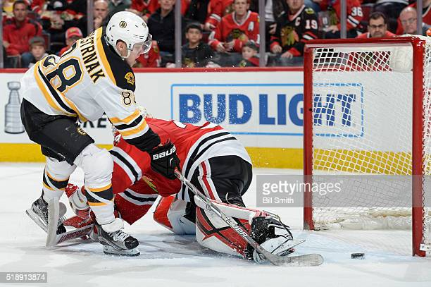 David Pastrnak of the Boston Bruins scores on goalie Scott Darling of the Chicago Blackhawks in the second period of the NHL game at the United...