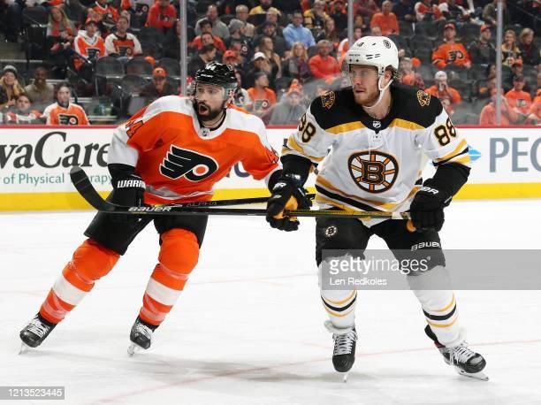 David Pastrnak of the Boston Bruins skates against Nate Thompson of the Philadelphia Flyers on March 10 2020 at the Wells Fargo Center in...