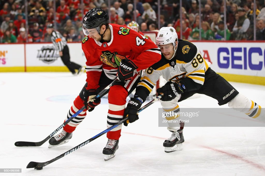 David Pastrnak #88 of the Boston Bruins tries to konck the puck away from Jan Rutta #44 of the Chicago Blackhawks at the United Center on March 11, 2018 in Chicago, Illinois.