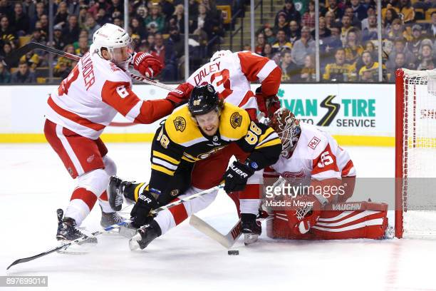 David Pastrnak of the Boston Bruins trips over Jimmy Howard of the Detroit Red Wings while taking a shot on goal during the first period at TD Garden...