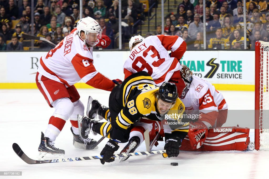 David Pastrnak #88 of the Boston Bruins trips over Jimmy Howard #35 of the Detroit Red Wings while taking a shot on goal during the first period at TD Garden on December 23, 2017 in Boston, Massachusetts.