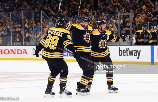 David Pastrnak, Patrice Bergeron and Brad Marchand of the Boston Bruins celebrate Bergeron's goal at 10:34 of the third period against the New York...
