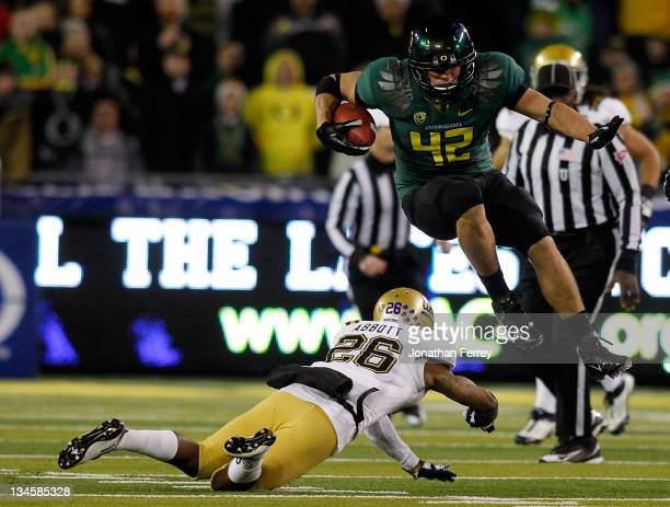 David Paulson of the Oregon Ducks leaps over Andrew Abbott of the UCLA Bruins during the Pac 12 Championship Game on December 2 2011 at the Autzen...